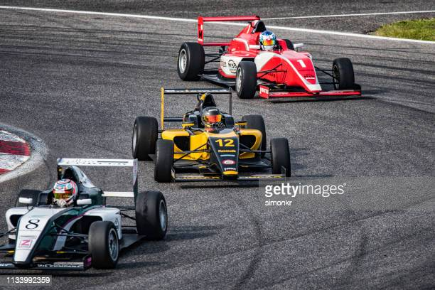 men driving formula racing cars - auto racing stock pictures, royalty-free photos & images