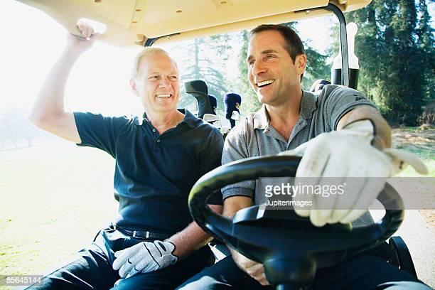Men driving golf cart