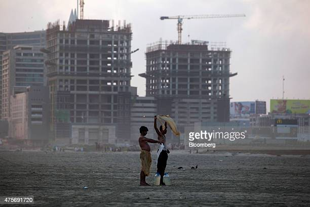 Men dry their clothes as towers stand under construction at Clifton Beach in Karachi Pakistan on Saturday May 30 2015 Pakistan's budget is scheduled...