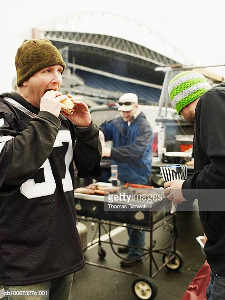 men eating food at tailgate party - tailgate party stock pictures, royalty-free photos & images