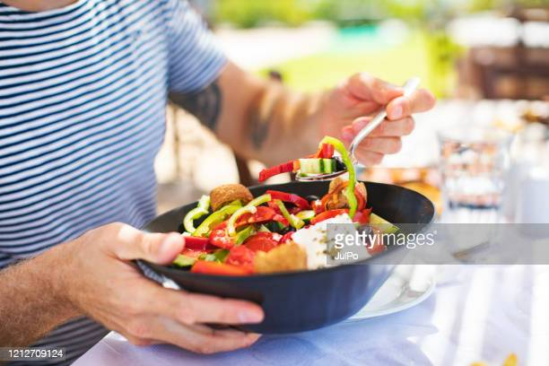 men eating greek salad - feta cheese stock pictures, royalty-free photos & images