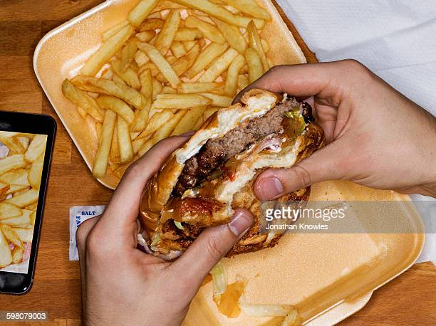 Men eating hamburger and fries, phone with picture