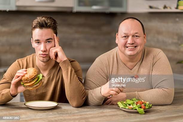 Männer Essen in der Küche und den Blick in die Kamera.