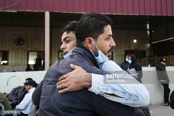 Men embrace as Palestinians wait to cross onto the Egyptian side through the Rafah border crossing between the Gaza Strip and Egypt on November 24...