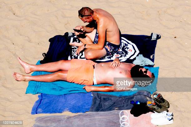 Men enjoy the sun and the warm weather during the heat wave at a beach.