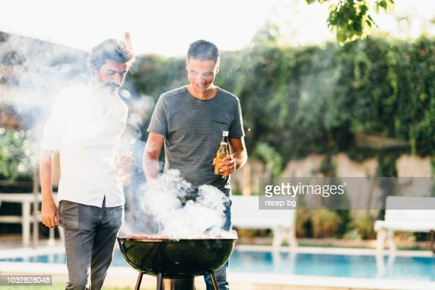men enjoying beer and chatting in backyard - barbecue social gathering stock pictures, royalty-free photos & images