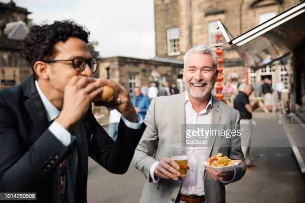 men enjoying burger, chips and beer outside - newcastle races stock photos and pictures