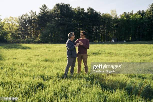 men enjoying discussion in grassy field - seulement des hommes photos et images de collection
