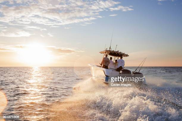 men enjoying in speedboat at sea against sky during sunset - fishing boat stock pictures, royalty-free photos & images
