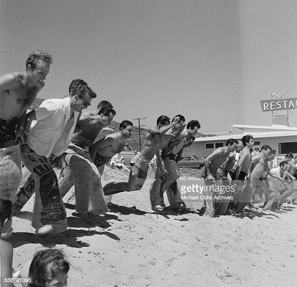 Men enter a sack race as actor Hugh O'Brian gives support during the Thalians Beach Ball in MalibuCalifornia