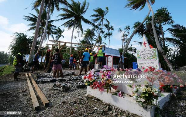 Men erect a temporary shelter for a funeral on August 15 2018 in Funafuti Tuvalu The graves of the dead are adorned and in many cases given pride of...