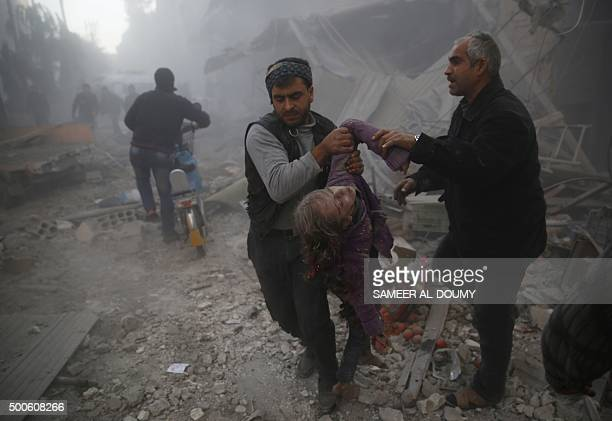 Men evacuate the body of a girl from under the rubble following reported airstrikes on the town of Hamouria in the eastern Ghouta region a rebel...