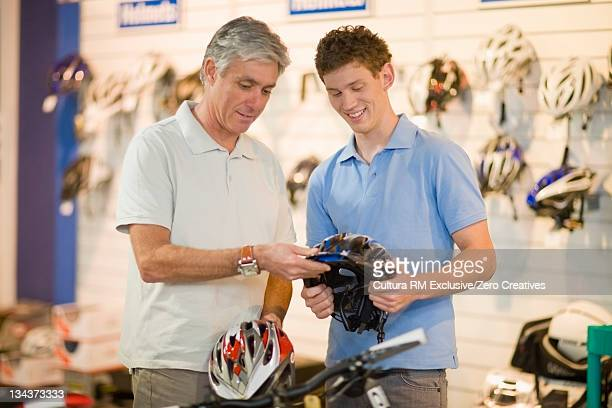 Men examining bicycle helmet in shop