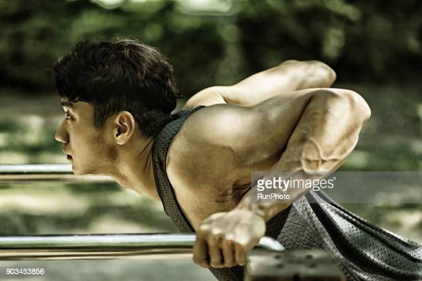 Men exercising on parallel bars