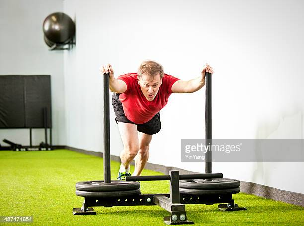 Men Exercising Weight Training with Push Sled in Health Club