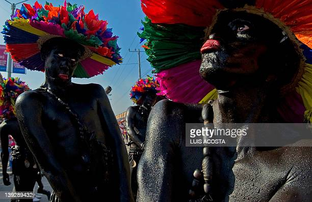 Men fancydressed as 'Son de Negro' take part in a carnival parade in Barranquilla Colombia on February 18 2012 Barranquilla's Carnival a tradition...