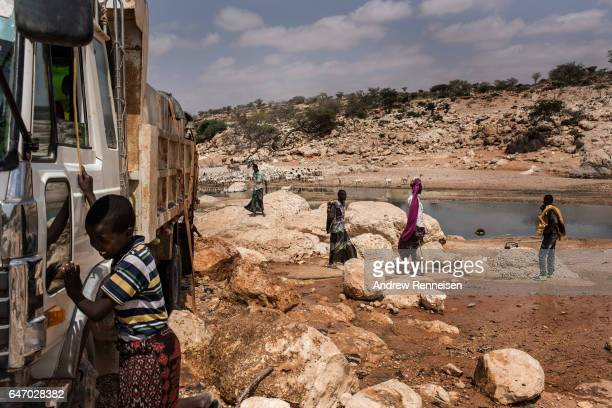 Men fill trucks with water from a nearly dried up riverbed on February 24 2017 in Dhudo Somalia People travel up to 75 kilometers to get water as it...