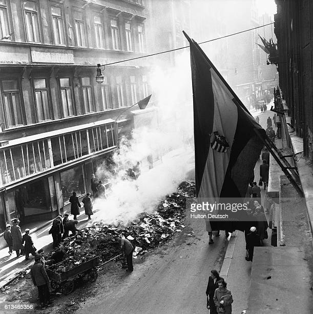 Men fill up a cart from a pile of smoking rubble on a Hungarian street during the 1956 anticommunist uprising which was brutally surpressed by...