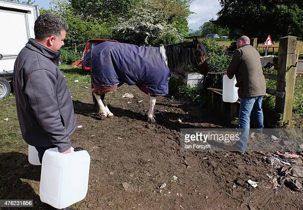Men fill water containers from a tap during the Appleby Horse Fair on June 7 2015 in Appleby England The fair is an annual gathering for Gypsy Romany...