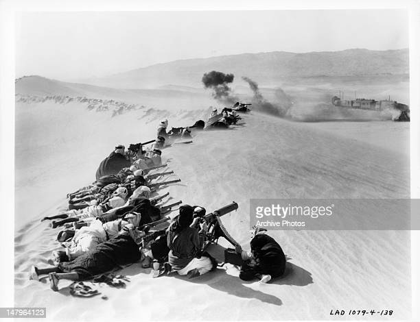 Men firing on train from sand dune in a scene from the film 'Lawrence Of Arabia', 1962.