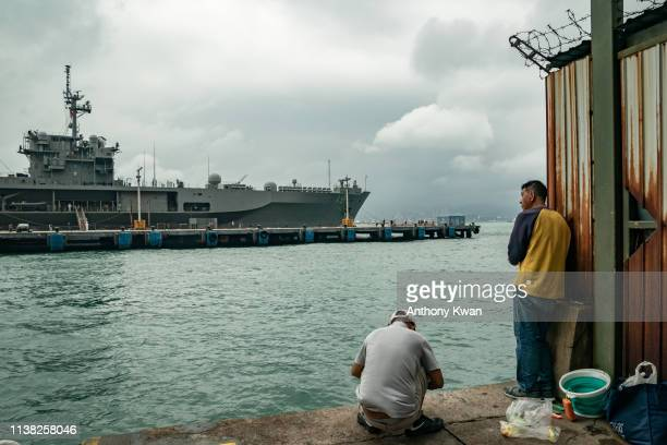 Men fish at a wharf in front of the USS Blue Ridge during a port call on April 20 2019 in Hong Kong China USS Blue Ridge is the first of the two Blue...