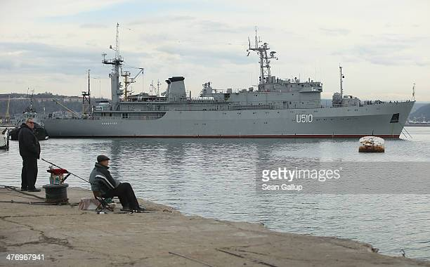 Men fish in the habrour as the Ukrainian naval command ship Slavutych stands behind on March 6 2014 in Sevastopol Ukraine Russian warships are...