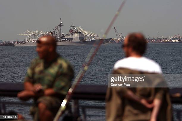 Men fish off a pier in Red Hook Brooklyn as the USS Monterey passes in the harbor during a parade of ships on the first day of Fleet Week May 21 2008...
