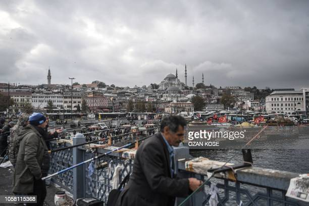Men fish on Galata bridge as the Suleymaniye Mosque is seen in the backround in Istabul's Eminonu district on November 6, 2018.