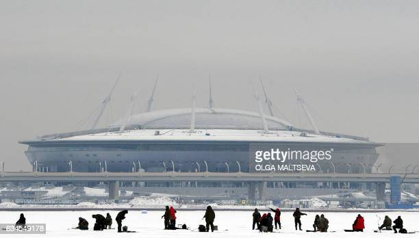Men fish through ice holes in the Gulf of Finland with Krestovsky football stadium also known as Zenit Arena and currently under construction for the...