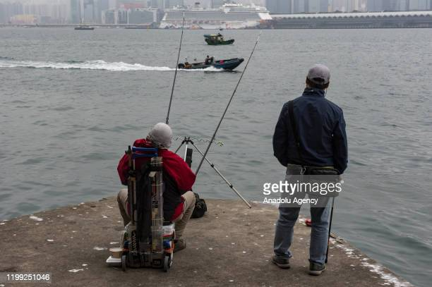 Men fish while behind stands at large the Dream World cruiser docking at Kai Tak Cruise Terminal in Kowloon Bay Hong Kong in Kowloon Bay Hong Kong...