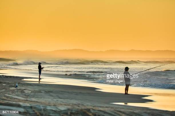 Men fishing at sunset,North Stradbroke Island,Queensland,Australia