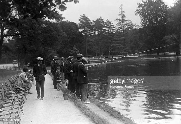 Men fishing in the lake of the Bois de Boulogne in July 1929 in Paris France