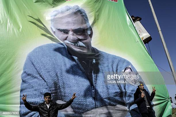 Men flash the 'V for Victory' sign near banner bearing a portrait of jailed Kurdish leader Abdullah Ocalan as they celebrate Newroz which marks the...
