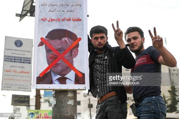 Men flash the victory gesture as they pose for a picture next to a sign condemning French President Emmanuel Macron, and depicting him with a pig...
