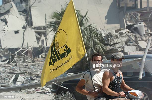 Men fly the Hezbollah flag as Lebanese battered by five weeks of war between Israel and Hezbollah return to the Hezbollah stronghold of Haret Hreik...