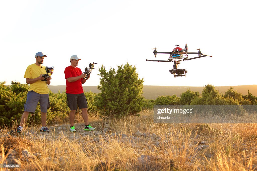 Men flying drone at sunset : Stock Photo