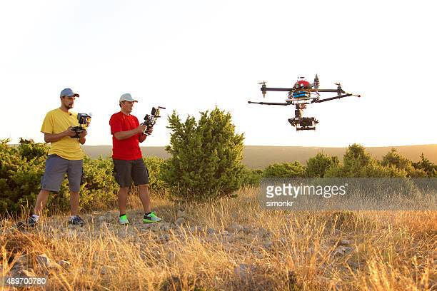 Men flying drone at sunset
