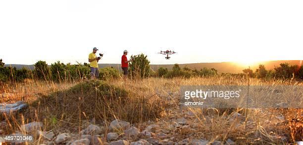 Men flying drone at sunset
