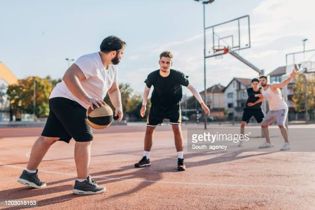 men friends playing basketball - blocking sports activity stock pictures, royalty-free photos & images