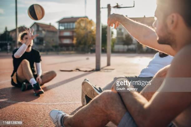 männer freunde entspannen nach streetball-match - ball passen stock-fotos und bilder