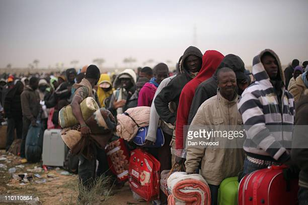 Men from Ghana queue for a coach during a huge sandstorm at a United Nations displacement camp on March 15 2011 in Ras Jdir Tunisia As fighting...
