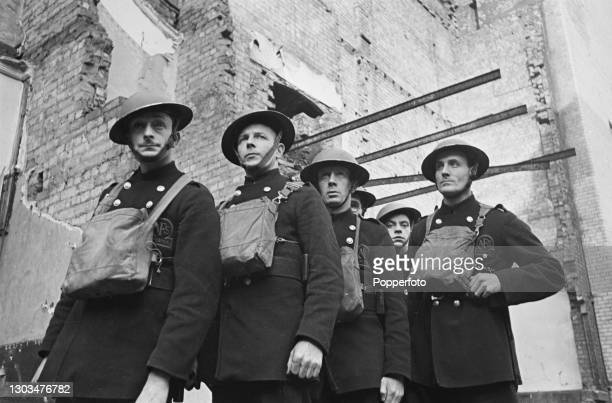 Men from the Liverpool Fire Brigade and the Auxiliary Fire Service pose together on a bomb site, created by German Luftwaffe air raids in the...