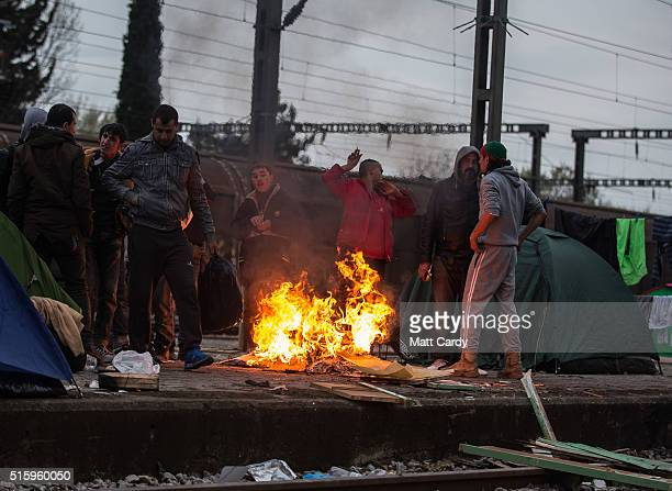 Men gather around a fire at the railway station at the Idomeni refugee camp on the Greek Macedonia border on March 16 2016 in Idomeni Greece The...