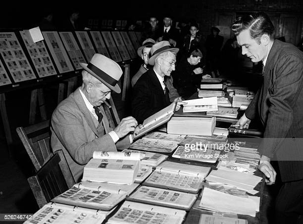 Men gather around a table full of postage stamps at a stamp show midcentury