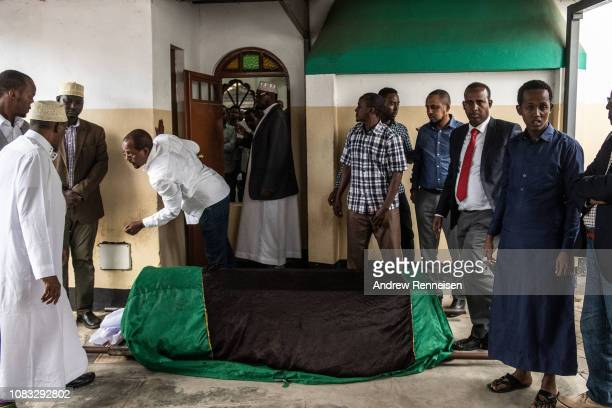 Men gather around the body of Abdalla Mohamed Dahir during a burial ceremony on January 16 2018 in Nairobi Kenya Dahir and his colleague were killed...