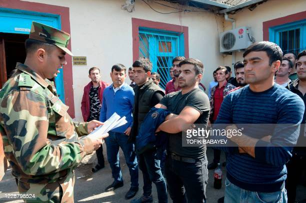 Men gather at a military commissariat in a settlement in Azerbaijan's Beylagan district on September 30 days after the country declared military...