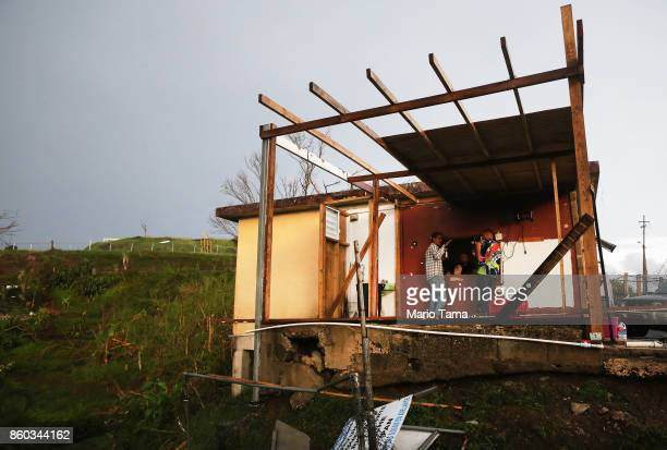 Men gather at a partially destroyed bar three weeks after Hurricane Maria hit the island, on October 11, 2017 in Aibonito, Puerto Rico. The area is...
