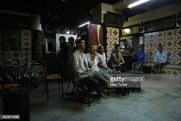 Men gather for coffee in the one of the cafes of the ancient medina of Tunis to celebrate the ending of the daily Ramadan fast although the country's...