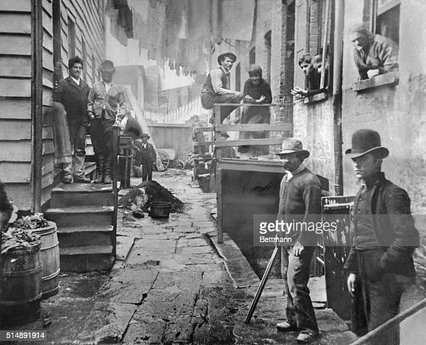 Men gather in an alley called Bandit's Roost in Manhattan's Little Italy Around the turn of the century this part of Mulberry Bend was a notoriously...