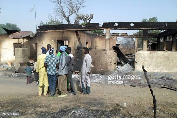 Men gather in front of a burnt house after Boko Haram attacks at Dalori village on the outskirts of Maiduguri in northeastern Nigeria on January 31...